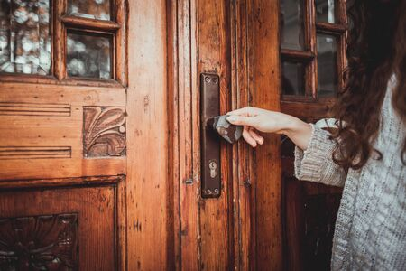Female hand holding on to the handle of an old stylish door