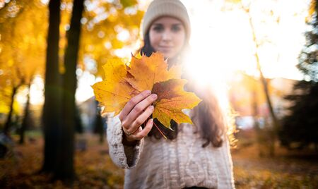 Outdoor lifestyle portrait of young woman with warm hat holding colorful autumn leaves and smiling