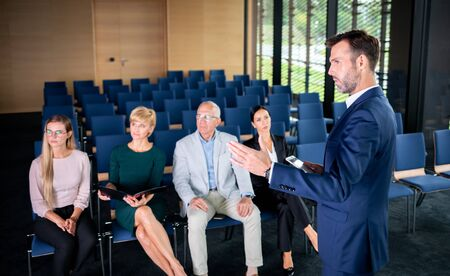 Business coach gesturing with hand while group of people sitting at the chairs in front of him