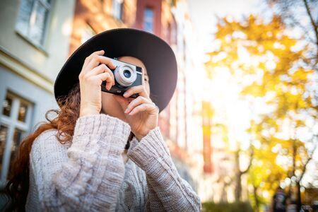 Beautiful stylish woman on city street at sunny day holding vintage retro camera Banco de Imagens