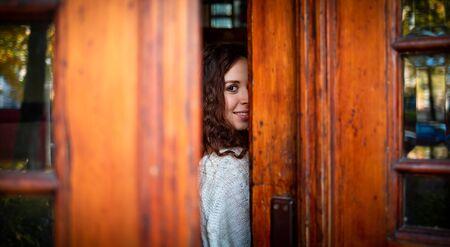 Young woman looking at camera in gap of the doors Banco de Imagens