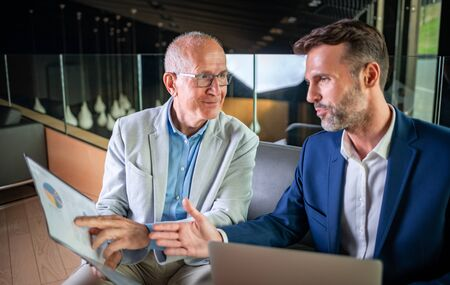 Younger and older businessman talking about documents during meeting in modern business lounge