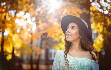 Pretty girl in hat standing on colorful autumn leaves background
