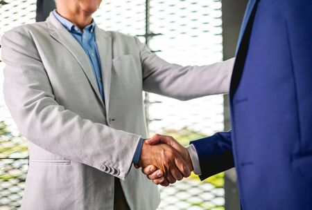 Business people shaking hands in the modern office finishing successful meeting Banco de Imagens