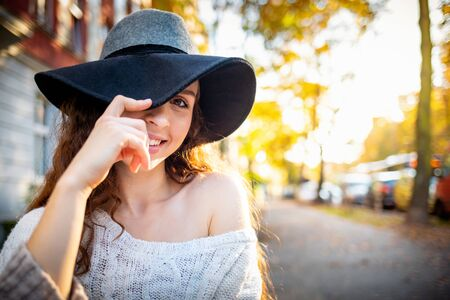 Portrait of beautiful stylish woman with big hat on city street at sunny day Banco de Imagens