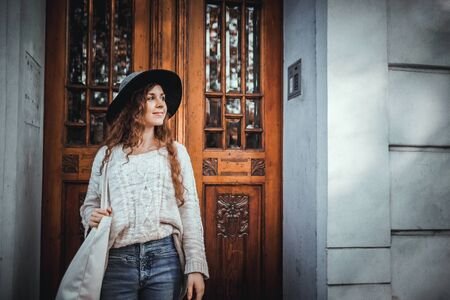 Young fashionable woman standing in old stylish door of building Banco de Imagens