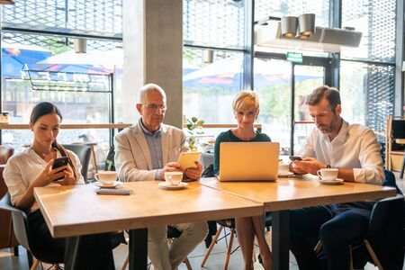Group of business people using electronic devices in cafe Banco de Imagens