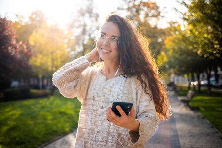 Portrait of a pretty smiling young woman using mobile phone while walking on city street