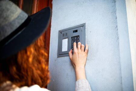 The female hand presses a button doorbell of home intercom
