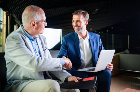 Younger and older businessman shaking hands in modern business lounge