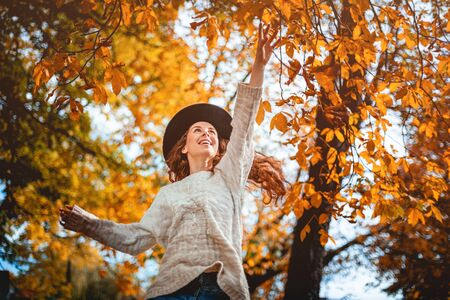 Smiling girl in hat jumping to colorful autumn leaves