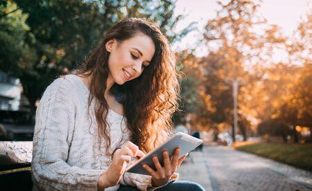 Joyful girl in autumn scenery using digital tablet outdoors browsing internet
