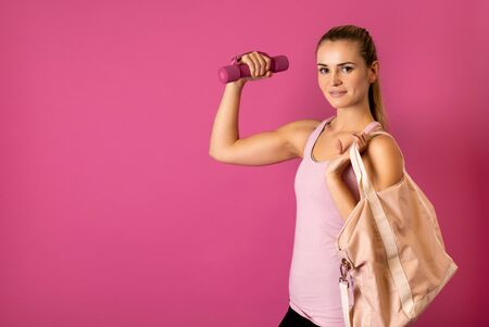 Young fit woman holding dumbell on pink background