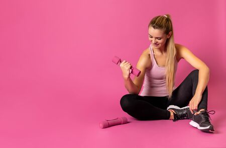Athletic woman with dumbbells sitting on pink background with copy space