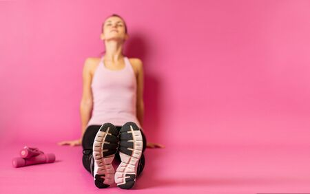 Young athletic woman sitting on pink background with copy space