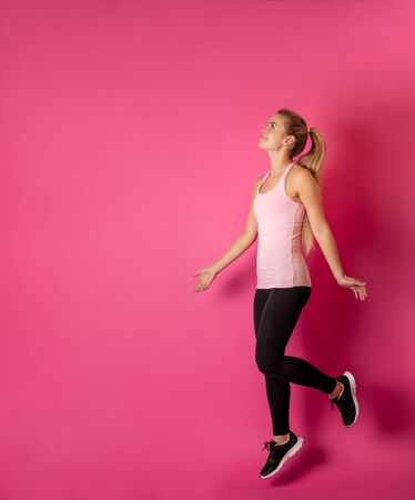 Young fit woman jumping on pink background with copy space