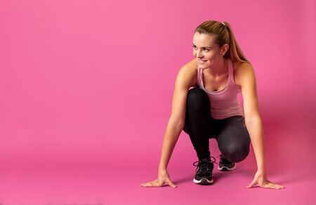 Fit woman on pink background at starting with copy space