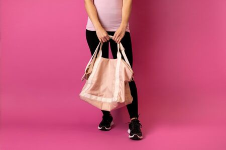 Fit woman with sport bag going to gym on pink background Stok Fotoğraf