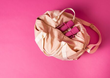 Women sports bag with dumbbells lying on pink background Stok Fotoğraf