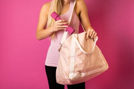 Fit woman packing the dumbbells into the sport bag on pink background