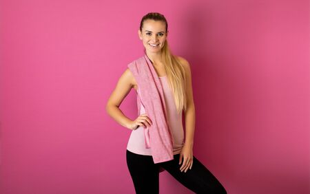 Fit woman after workout with towel on her shoulders on pink background Stok Fotoğraf