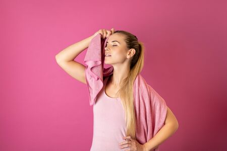 Young fit woman tired after workout with towel on her shoulders on pink background