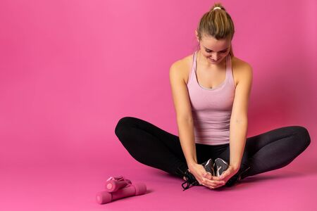 Athletic woman stretching exercise on pink background