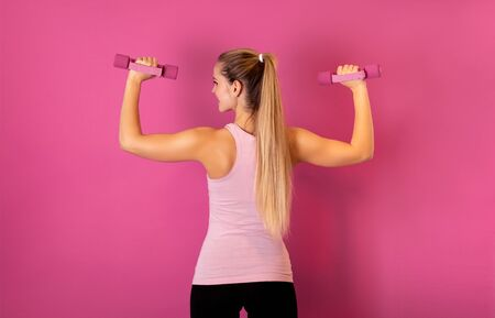 Attractive fitness woman holding dumbells on pink background