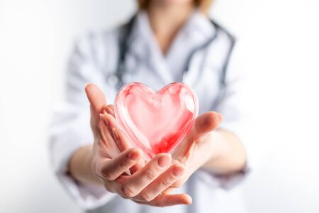 Female cardiologist doctor holding red heart on hands