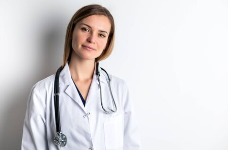 Medical concept of young female doctor in white coat with stethoscope copy space
