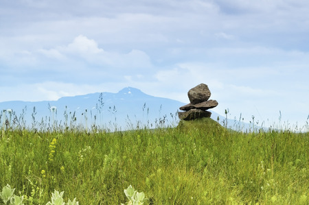 cairn: Stone Cairn on Green Meadow Stock Photo