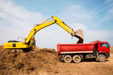 Loading of earth soil into the body of a cargo dump truck by an excavator bucket