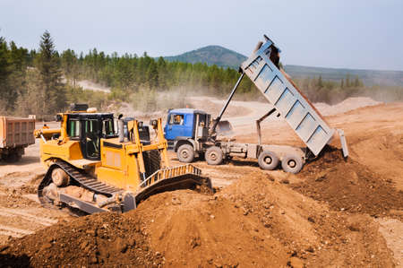 Unloading of earthen soil by side dump trucks, the bulldozer levels the soil