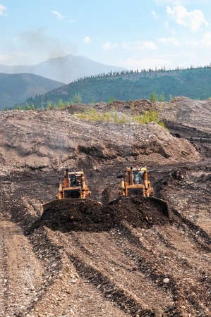 Bulldozers rake gold-bearing mountain soil into a heap, then this soil will be washed on an industrial device in order to extract natural gold. Eastern Siberia