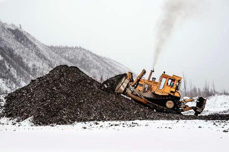 Early winter. Bulldozer rakes a pile of mountain soil in a mountainous area