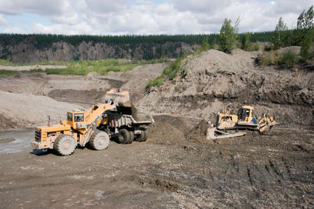Wheel loader in a mountainous area loads a mining truck with a bucket, dumping the mountain soil into it. Gold mining industry. Archivio Fotografico