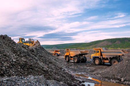Excavation in a mountainous area, dump trucks queue up to be loaded in a mining quarry. A bulldozer is working nearby.