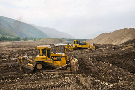 Mining of natural gold in a mountainous forest area. Bulldozers in the process of working in a mountain forest area on a summer sunny day