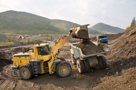 Front-end loader loads gold-bearing mountain soil into the back of a mining truck in a mountainous area. 版權商用圖片