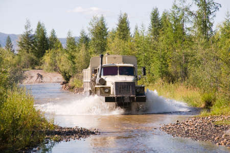 Lorry - a fuel tanker overcomes a water obstacle in a mountainous wooded area. The water level in mountain rivers and streams is constantly changing after rains