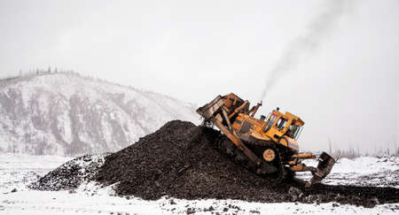 Winter in a wooded mountainous area. A bulldozer shovels a pile of mountain soil in which there are minerals. Seasonal shift work in mountainous areas.