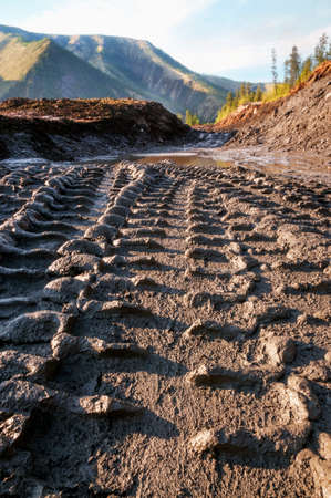 Wheel print on a wet mountain dirt road in an industrial area where a lot of construction and earthmoving equipment is operating