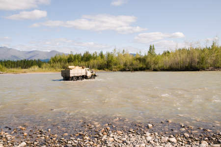 A gasoline tanker crosses a river in a wooded mountainous area in Eastern Siberia; a common sight in remote areas of Siberia, where there are still very few roads and bridges