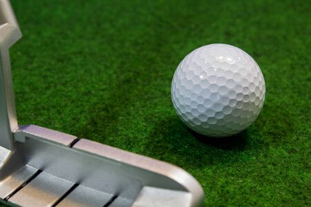 Putter, golf ball and green for the relaxed office life