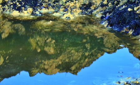 yellow clay is reflected in a puddle Фото со стока