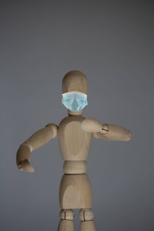Statue of wood with a mouth and nose mask, as protection against viruses