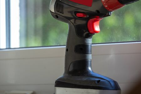 Operating a cordless screwdriver in front of the window