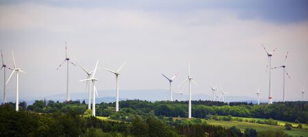 large piece of forest and in the middle of it a large wind farm with many wind turbines