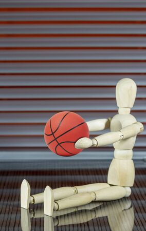Wooden dummy with basketball in front of a jalousie plays with the ball Фото со стока