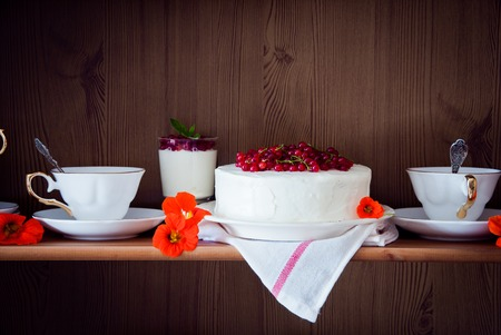 dessert stand: Cakes with red currant decorated with fresh red berries and flowers,  with cups of tea on shelves